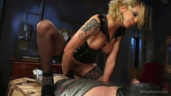 Angry female friend in latex corset punishes anal passage opening associated with a perverted involved stud