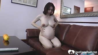 Busty pregnant chick poses on the couch